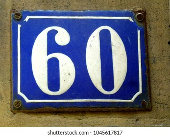 vintage enamel house number 60, white digits on blue background, with four screws