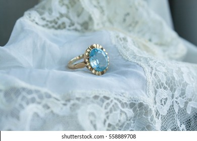 vintage engagement ring with aquamarine stone over a white lace cloth