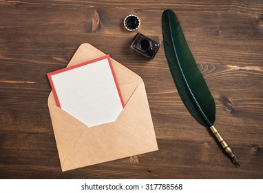 Vintage envelope with empty card and quill pen on wooden table top view
