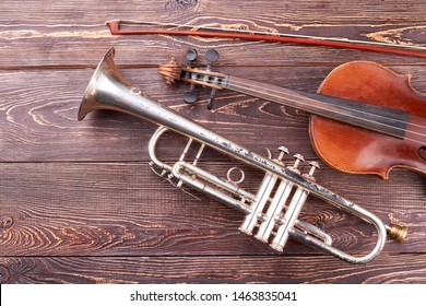 Vintage equipment of orchestra music. Violin, fiddle stick and trumpet on brown textured wood.