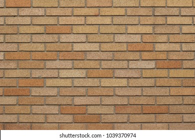 Vintage exterior brick wall background in traditional common bond pattern with hues of yellow, gold, tan, beige, and orange