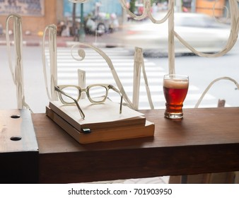 Vintage eyeglasses , books and a glass of beer on wooden counter with daylight from window in the evening. Background outside is the street.