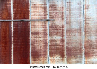 a vintage faced rusted red metal factory warehouse wall