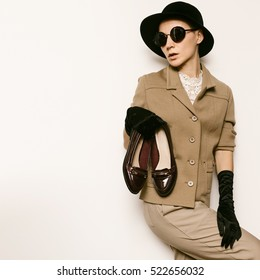 Vintage Fashion Lady Beige classic costume and stylish Accessories. Black Gloves. Hat. Fashion concept. Retro Time Trend Vintage Shoes