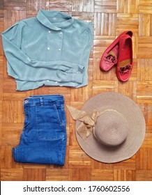 Vintage fashion outfit concept - teal shirt, jeans, red shoes and a summer hat. On wooden background.