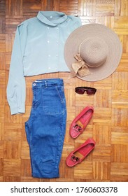 Vintage fashion outfit idea for women with a teal shirt, jeans, red shoes, sunglasses and a summer hat. On wooden background.