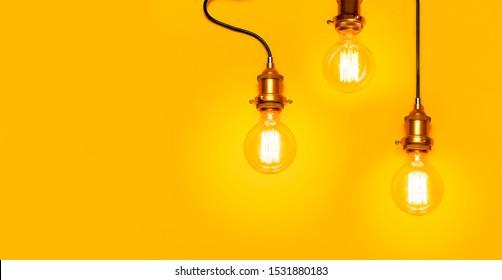 Vintage-modische Edison-Lampe auf hellgelbem Hintergrund. Die oberste Ansicht flach legt Kopienraum. Kreatives Konzept, Designerlampe, modernes Interieur. Licht, Elektrizität, Hintergrund mit Lampe