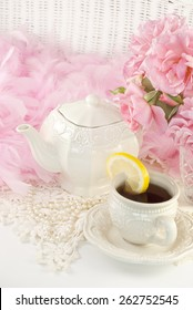 A vintage feminine tea party still life, with a teapot set, hot tea with lemon and fresh cut pink roses, perfect for Mothers Day, Easter or special occasion