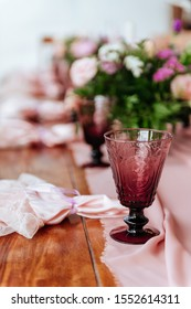 Vintage festive table setting with pink roses, candles and cutlery on an old wooden board