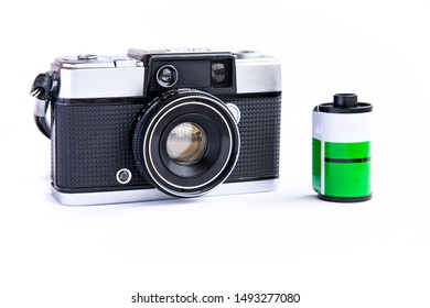 Vintage film camera with 35mm film cartridge isolated on white background.