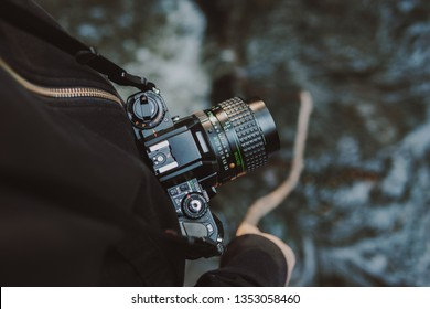 Vintage film camera around woman neck while she holds a stick into a river.