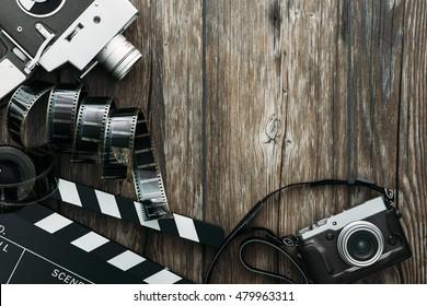 Vintage film camera, clapper board, filmstrip and old camera on a desktop, cinema and videomaking concept