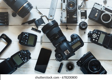 Vintage Film Camera, Digital Camera And Smartphone On White Wooden Background Technology Development Concept. Top View
