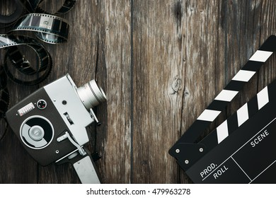 Vintage film camera, filmstrip and clapper board on a wooden desktop, cinema and filmmaking concept