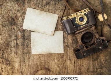 Vintage film camera and old photos on wooden background. Nostalgic still life