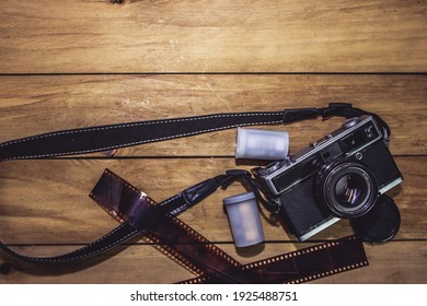 vintage film camera and film on wooden table.