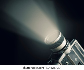 Vintage film camera with projecting spotlight over black background. Cinema art and entertainment industry.