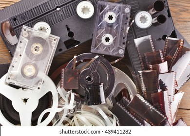 Vintage film camera rolls, old audio and video casettes with tape and foto strip on wooden background