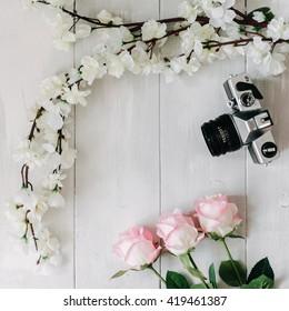 Vintage film camera, sakura branch, pink rose flowers on the white wooden desk. Top view, flat lay