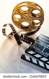 Vintage film claper with film reel placed on wood. Filmammakers equipment background