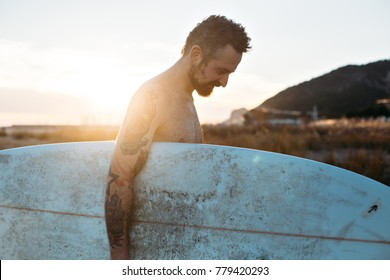Vintage film effect photo of middle aged man with beard and authentic hipster body tattoos, walks on sunny sunset or sunrise beach with surf board under arm, chill and relax atmosphere and lifestyle