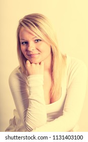 Vintage Film look shot of a pretty blonde young adult woman in the studio