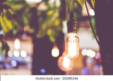 Vintage filter : Vintage lightbulb hanging on tree.