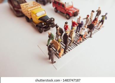 Vintage filter top view of miniature toys of crowd walking on zebra crossing with vehicles stopped concept.