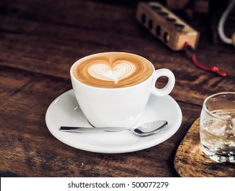 Vintage filtered,white coffee cup with heart shape latte art on wood table.