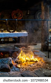 Vintage fireplace for cooking food inside the old wooden viking longhouse in the reconstruction of ancient village. Interior of viking house.