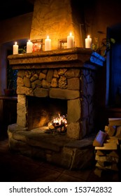 Vintage fireplace room interior. Chimney place, candles fire woodpile. Romantic still life scene