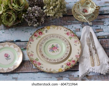 Vintage floral dinner plates on a distressed wood table, with vintage cutlery, napkin and hydrangeas
