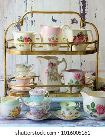Vintage floral milk jug pitchers and tea cups on a gold cake stand on distressed wood rustic table - high tea party