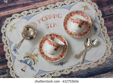 Vintage floral tea cups and saucers on an embroidered table cloth, tea party