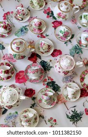 Vintage floral teacups and saucers flatlay on a flower background - green cake stand - spring high tea party