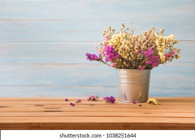 Vintage flowers on wooden table over blue rustic wall background