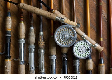 Vintage Fly Rods Reels artistic display of many old fishing rods on flat lay