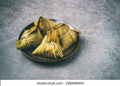 Vintage food photography of Zongzi or Chinese sticky rice dumpling for dragon boat festival on grey cement table top, selected focus.