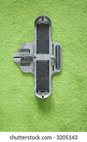 Vintage foot size measuring device against green carpet.