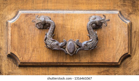Vintage front door in the medieval city of Italy. Ancient wooden gate. Old city streets, beautiful doors and unusual door handles. Door Handles in the shape of fish or dragons.