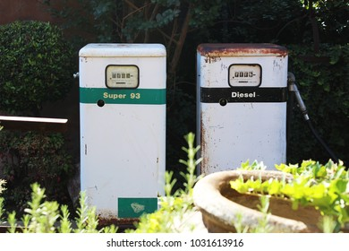 Vintage fuel pumps discarded in green garden