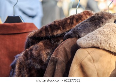 Vintage fur coats at a flea market in Europe. Used leather and suede clothing on garage sale or charity shop. Dry cleaning