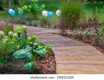 Vintage garden path made of wooden planks. Green lawns, flowers, white & blue ballons. Closeup.