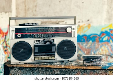Vintage ghetto blaster with plenty of musical cassettes on grungy background with graffiti.