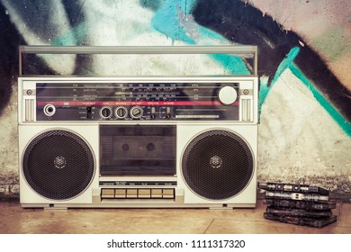 Vintage ghetto blaster with plenty of musical cassettes on grungy background with graffiti. Remembering and listening to music from the past.