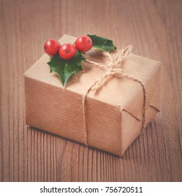 vintage gift box, kraft paper, rope and holly berries on old wooden background, toned