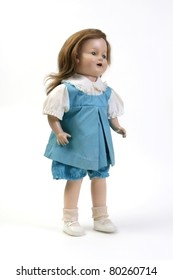 Vintage girl baby doll wearing blue & white dress standing on white background