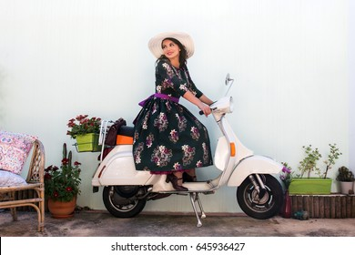 Vintage girl with beautiful floral dress next to a classic motorcycle.