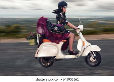Vintage girl riding a classic motorcycle on the countryside road.