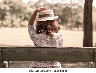 Vintage Girl sit in park,, holding her hat for wind blow
